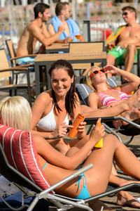 Young woman sunbathing and talking lying on deckchair summer