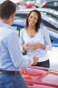 Young woman talking to car salesman in lot