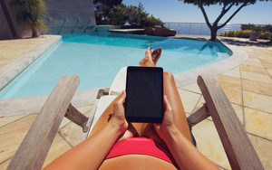 Young woman using a tablet PC near the pool. User POV. Female model relaxing on a deckchair holding digital tablet.