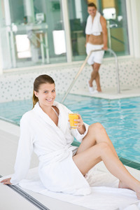 Young woman wearing bathrobe relax at swimming pool,drink juice
