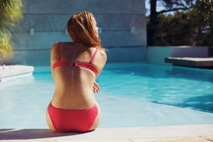 Young woman wearing red bikini enjoying summer at the swimming pool. Caucasian female model sitting on the edge of the pool.