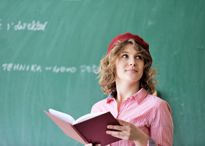 Young woman with a red cap holding a book in a classroom