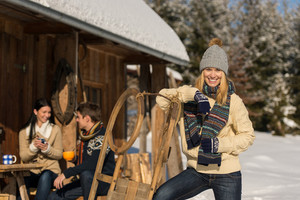Young woman with friends spending holiday in winter snow cottage