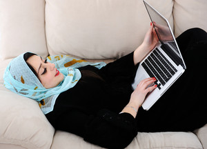 Young woman with laptop lying on couch