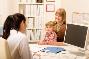Young woman with little daughter having consultation at pediatrician office