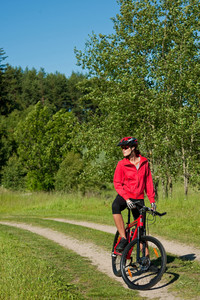 Young woman with mountain bike in the nature on a sunny day