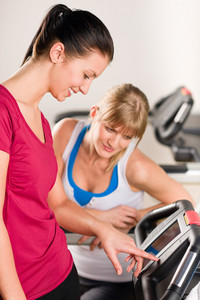 Young women exercising at fitness center on treadmill machine