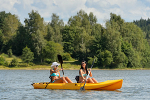 Young women in bikinis kayaking on river summertime