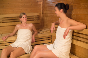 Young women talking while relaxing in sauna
