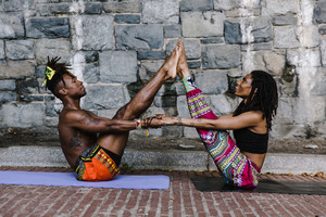 A man and woman hold each other up in a yoga pose