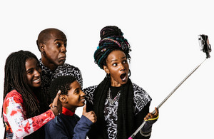 african american family of four takes picture with a selfie sticks