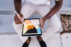 African American man drawing on tablet
