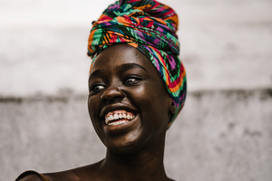 African lady in a multicolored headwrap laughing