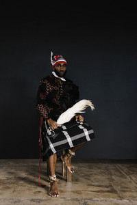 african man in nigerian clothing and head covering holding a flywhisk