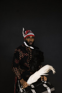african man in nigerian clothing and head covering holding a stick with fur