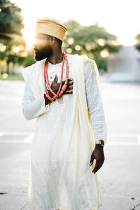 african man in traditional clothes standing with hand over his heart