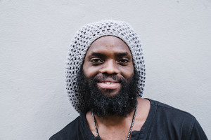 African man smiling against the wall