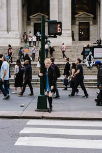 Albino woman standing on busy sidewalk