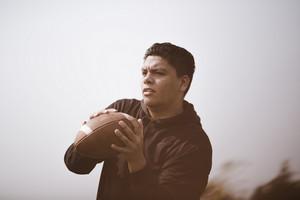 American Indian and Alaska Native man holding a football