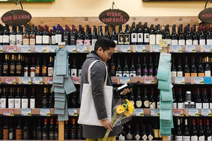 asian man shopping for wine with flowers in hand