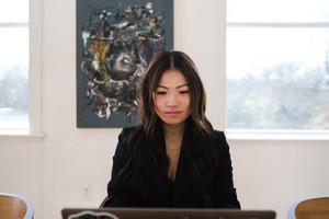 Asian woman looking at computer
