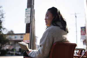 asian woman sitting in a chair outside looking away from camera holding a book and pen