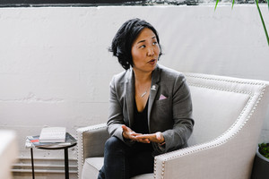 asian woman sitting in chair talking