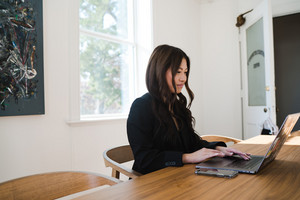 Asian woman typing on computer