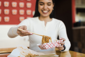 asian woman with noodles and chopsticks