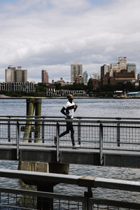 athletic man runs around a dock of water