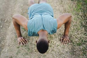 athletic man runs down dirt track