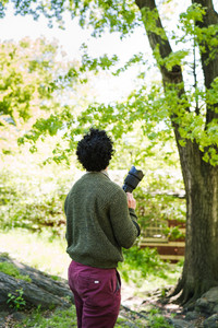 back of man with dark curly hair wearing green sweater and purple pants holding camera