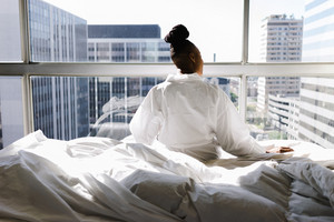 back view of black woman sitting on bed looking outside window