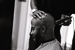 barber working on a male client's hair as he sits in a chair