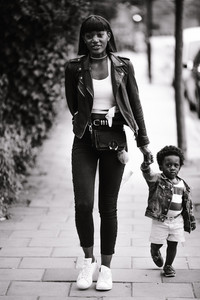 Black-and-white image of mother and child walking holding hands