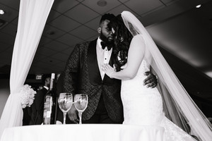 Black and white photo of interracial couple praying at wedding