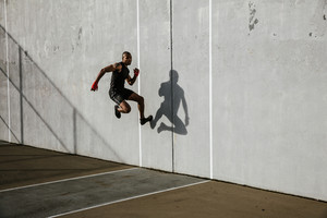 black athletic man jumping off wall