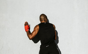 Black athletic man leaning against a wall
