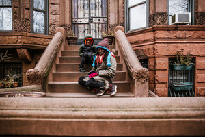black boy and girl sitting on building's steps duing winter
