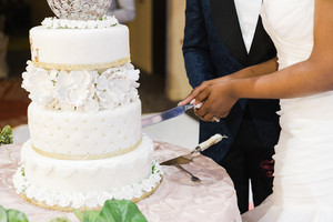 black bride cutting into wedding cake