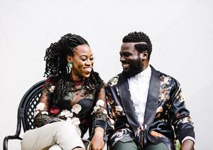 black couple in a flowery attire sitting in a chair smile
