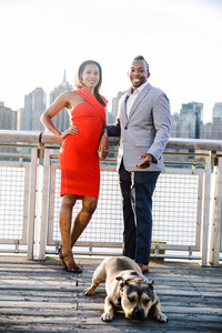 Black couple posing with their dog on a pier