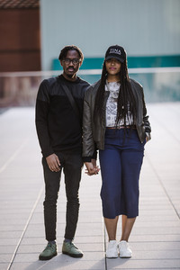 Black couple standing in front of a building