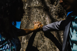 Black couple take engagement pictures by a tree