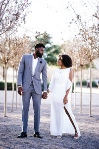 black couple taking wedding photos outside by trees