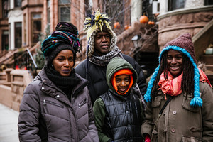 black family of four in winter clothing stand outside smiling