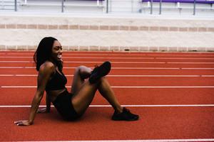 Black female athlete stretching her leg on a track