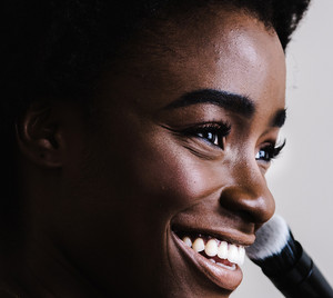 Black female model smiles as she puts on blush