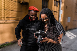 black female photographer showing photos to model in front of mustard colored building