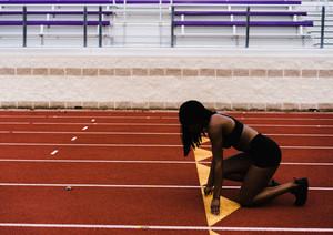 Black female prepares to run down the track